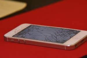 Un iphone blanc sur fond rouge avec écran cassé