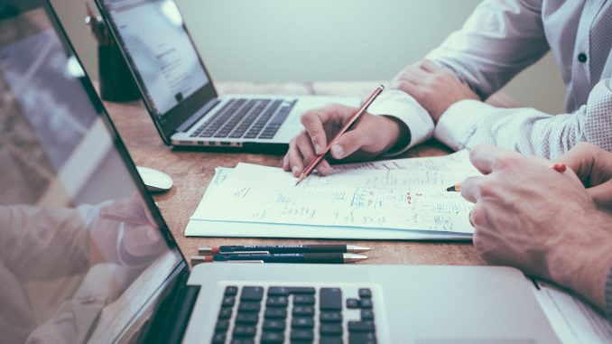 deux personnes travaillant sur ordinateur portable papier stylo