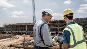 Des ouvriers travaillant sur un chantier avec une tablette durcie