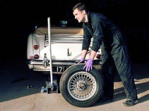 Mécanicien en train de changer un pneu de voiture
