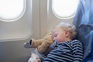 Bébé blond endormi sur sa peluche ours durant un vol en avion