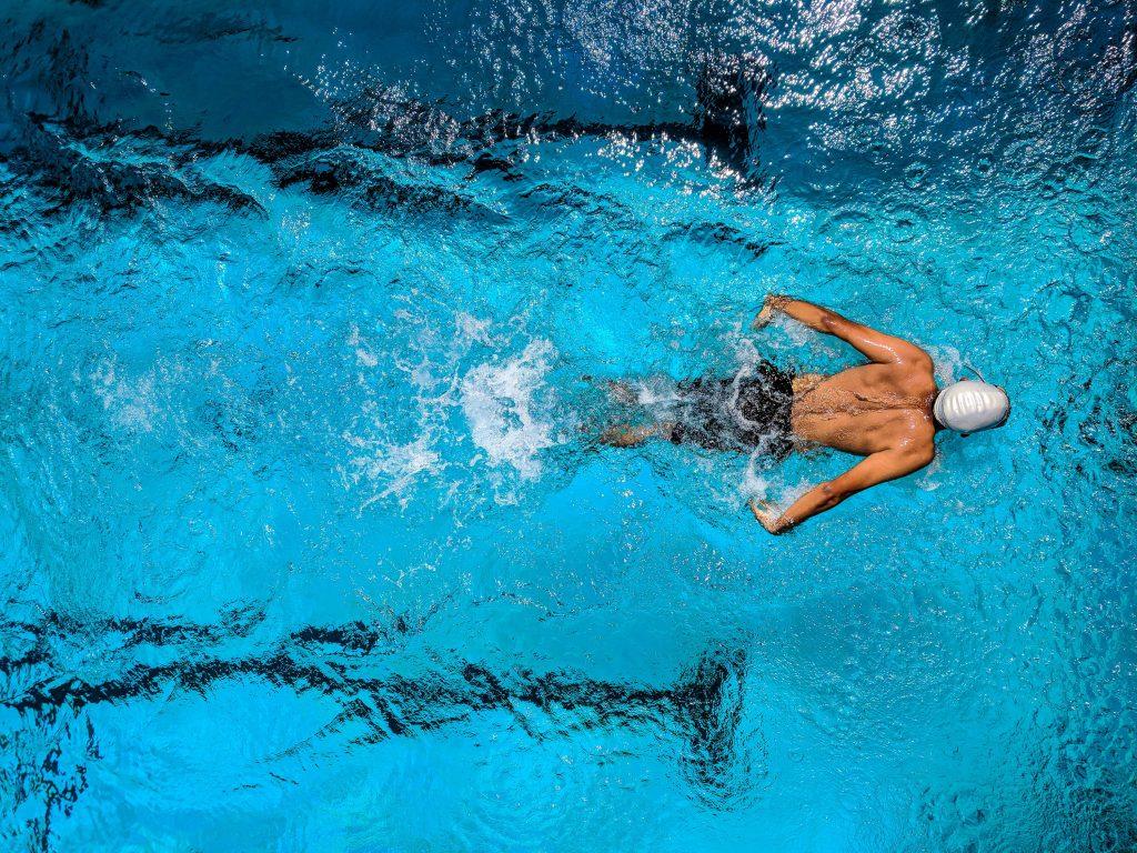 Homme qui fait des longueurs dans une piscine