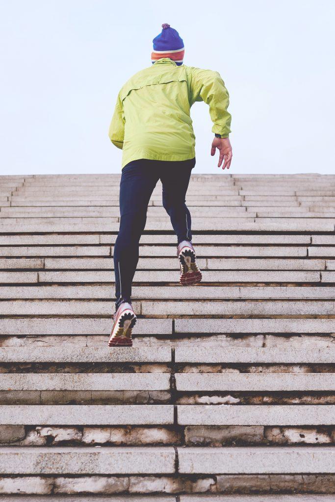 personne de dos faisant du running dans des escaliers portant un bonnet une veste verte un collant de sport et des baskets
