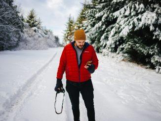 homme sur une route enneigées portant une doudoune rouge un bonnet jaune et un pantalon noir