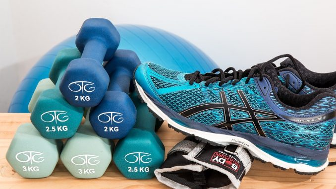 chaussure de sport posée à côté de poids de musculation